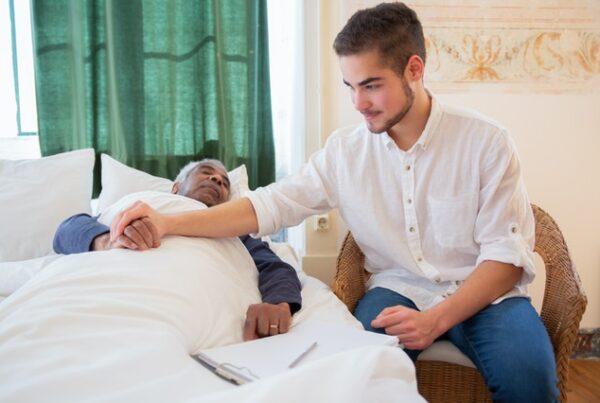 man sitting next to an elderly man lying in bed